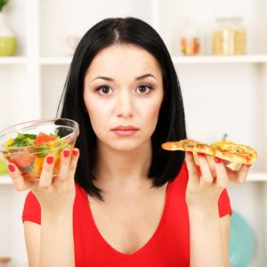 Pretty girl selects pizza or diet on kitchen background; Shutterstock ID 135259418; PO: aol; Job: production; Client: drone