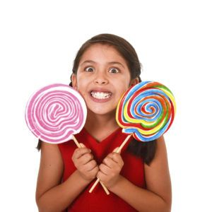 happy female child wearing red dress holding two big lollipop in crazy funny face expression in sugar addiction and kid love for sweet candy concept isolated on white background